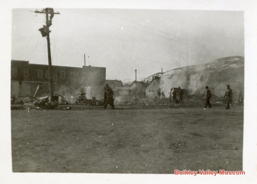 The final mystery photo showing men picking their way through the smoking ruins of a building.